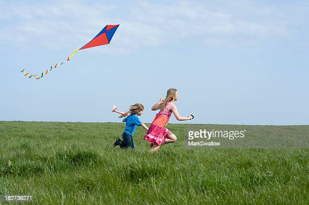 Two young children outside on a sunny day kite flying