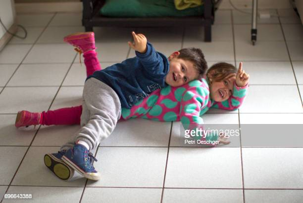 Two young children playing on the floor.