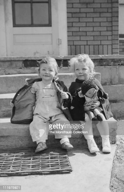 Two young children sitting on an outside porch step one holding her rag doll the other removing her coat showing off her dungarees America1946