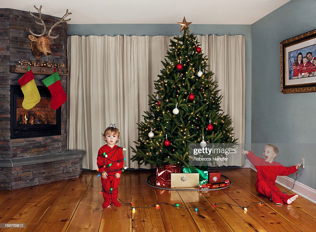 Two young children wrapped in Christmas lights : Stock Photo