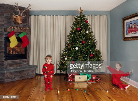 Two young children wrapped in Christmas lights