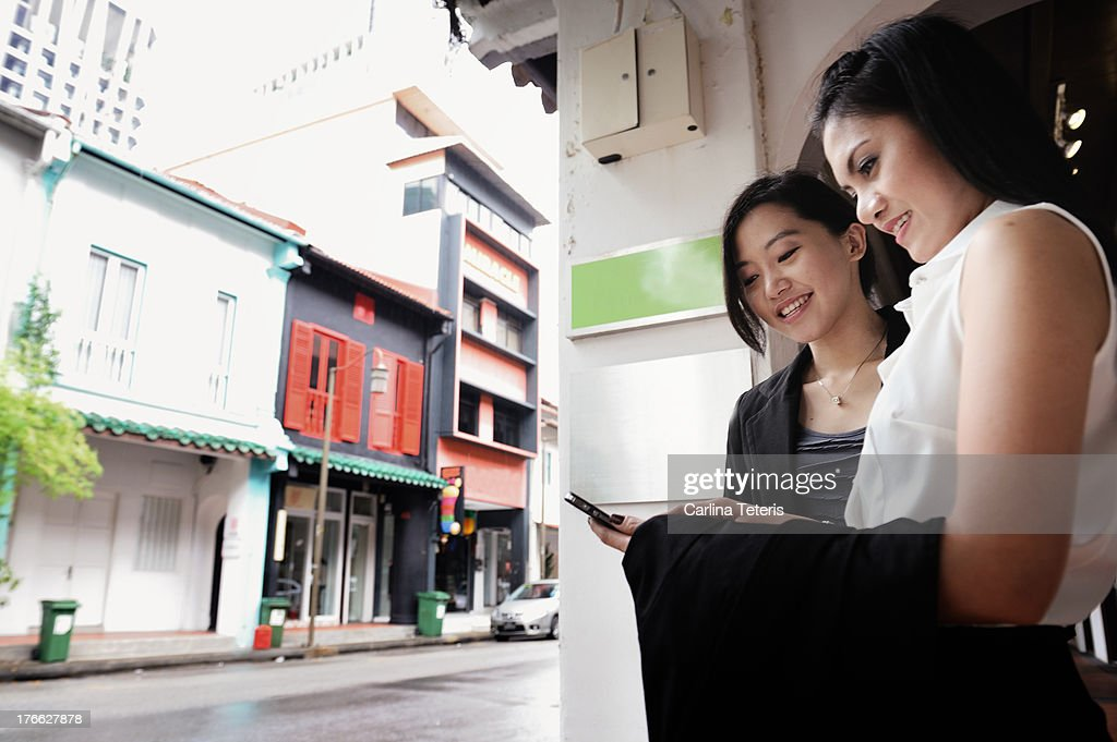 Two young colleagues checking a smart phone : Stock Photo