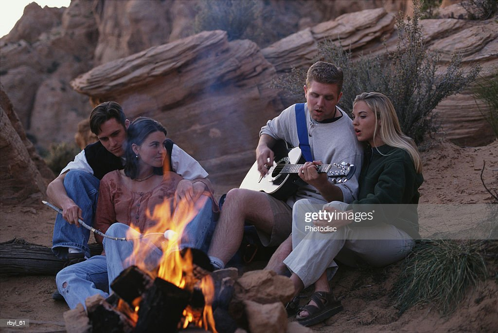 two young couples are sitting around a campfire raosting marshmallows and singing songs on the guitar : Stock Photo