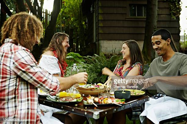 Two young couples dining in garden laughing