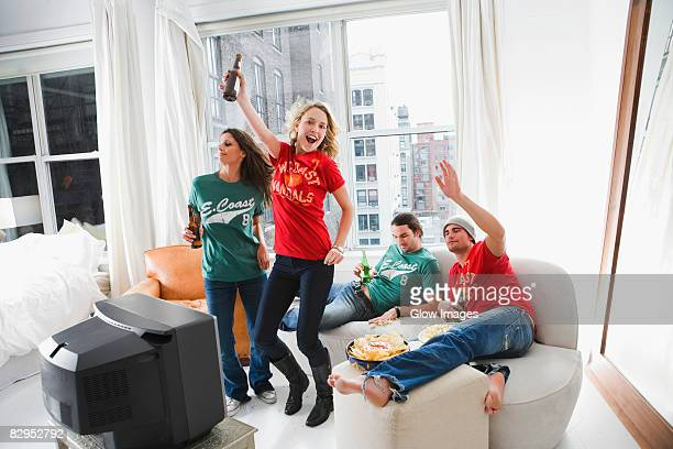 Two young couples enjoying beer and dancing in a living room