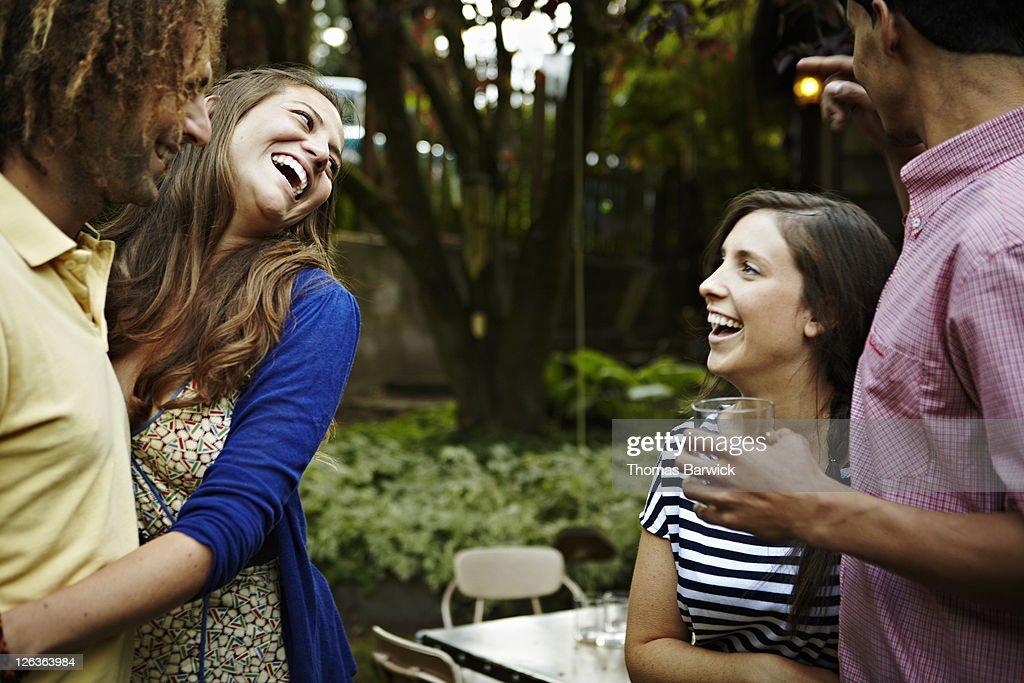 Two young couples in backyard garden laughing : Stock Photo