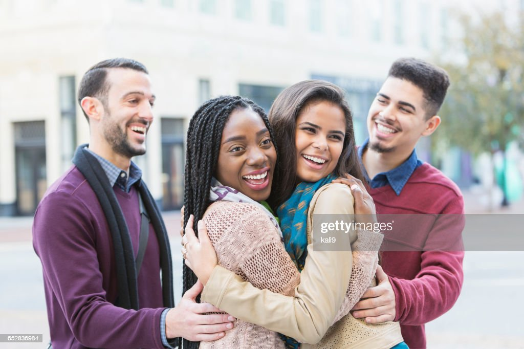 Two young couples meeting, greeting on city street : Bildbanksbilder
