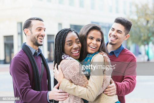 Two young couples meeting, greeting on city street : Stockfoto