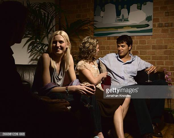 Two young couples on sofa, each holding separate conversations