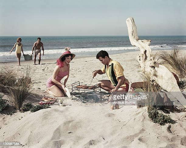 Two young couples preparing barbeque food at beach