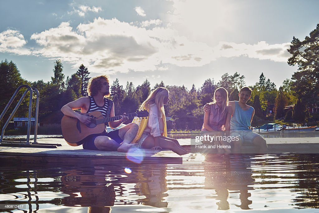 Two young couples relaxing on pier, Gavle, Sweden : Stock Photo