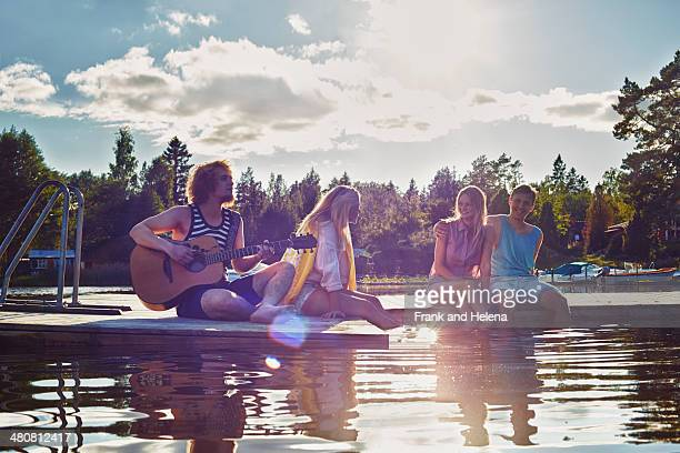 Two young couples relaxing on pier, Gavle, Sweden