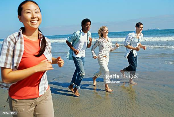 two young couples running on the beach