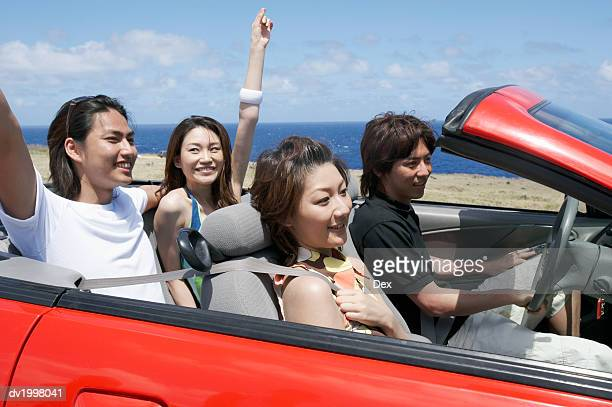 Two Young Couples Sit in a Convertible, Driving by the Sea