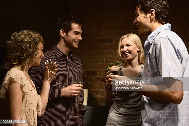 Two young couples socializing, holding drinks and laughing