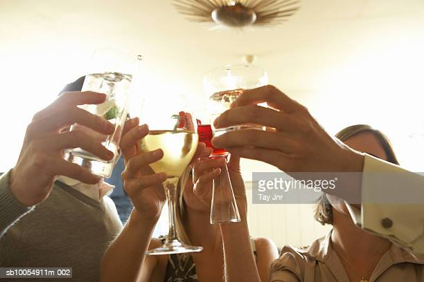 Two young couples toasting with drinks, close-up of hands
