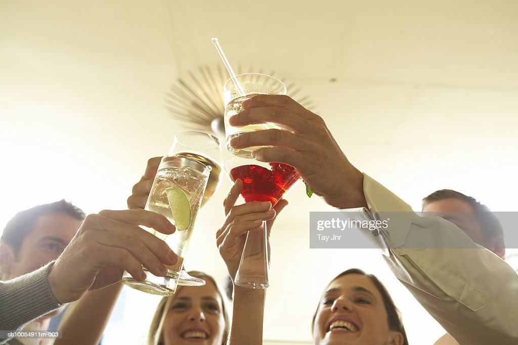 Two young couples toasting with drinks, close-up of hands : Stock Photo