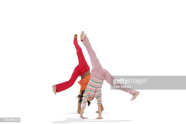 Two young doing cartwheels