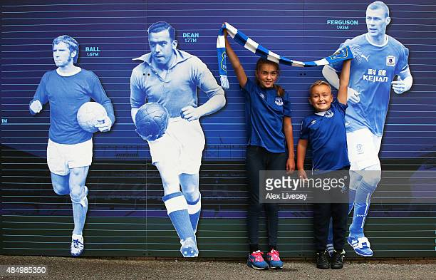 Two young Everton supporters pose in front of a mural prior to the Barclays Premier League match between Everton and Manchester City at Goodison Park...
