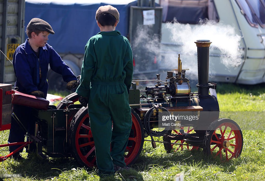 Two young exhibitors prepare their minature steam engine to shows at the Cornish Steam and Country Fair at the Stithians Showground on August 16, 2013 near Penryn, England. The annual show, now in 58th year, is one of Cornwall's largest outdoor events and is one of the UK's most popular and respected steam rallies.