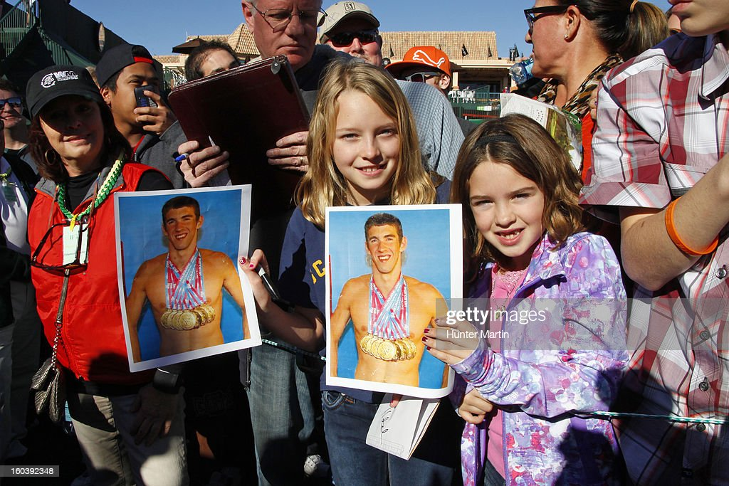 Two young fans of <a gi-track='captionPersonalityLinkClicked' href=/galleries/search?phrase=Michael+Phelps&family=editorial&specificpeople=162698 ng-click='$event.stopPropagation()'>Michael Phelps</a> wait for an autograph on the 18th hole during the Wednesday Pro-Am of the Waste Management Phoenix Open at TPC Scottsdale on January 30, 2013 in Scottsdale, Arizona.