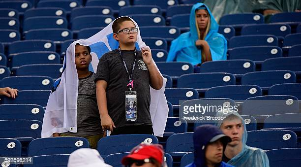 Two young fans of the Tennessee Titans remain in the stands after a delay due to lightning during the second half of a game against the Carolina...
