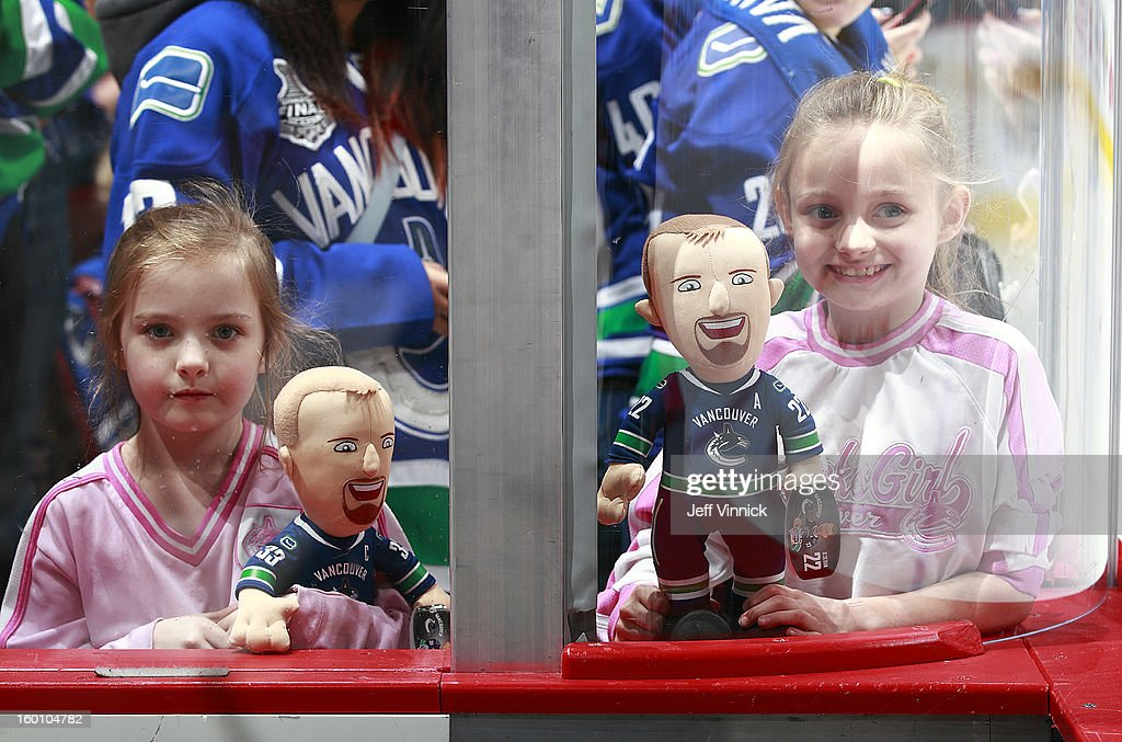 Two young fans show off their Daniel Sedin and Henrik Sedin dolls before the season-opening NHL game between the Anaheim Ducks and Vancouver Canucks at Rogers Arena January 19, 2013 in Vancouver, British Columbia, Canada.