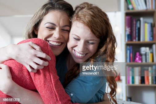 Two young female friends at home embracing
