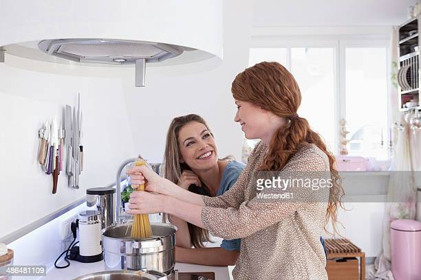 Two young female friends cooking together