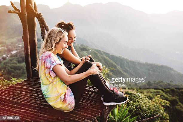 Two young female friends on balcony over Lake Atitlan, Guatemala