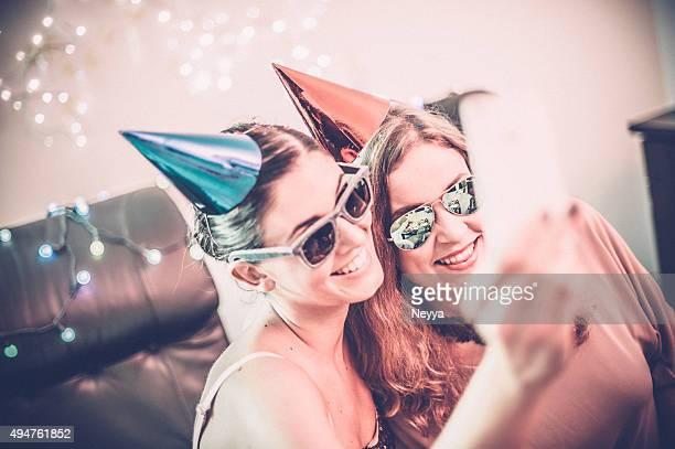 Zwei junge weibliche Freunde nehmen Selfie während der Party