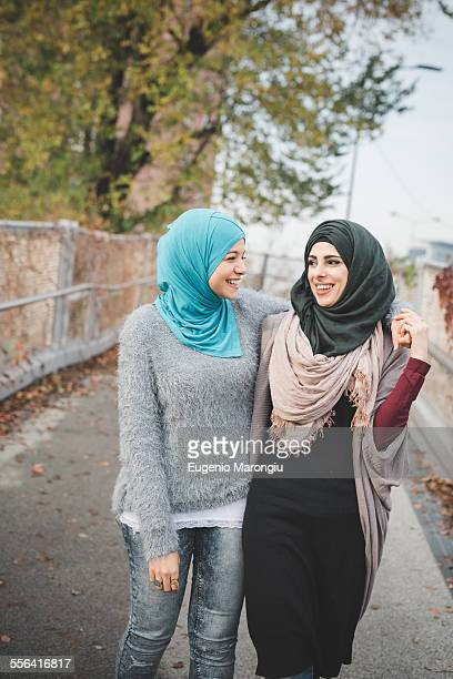 Two young female friends walking and chatting on park path
