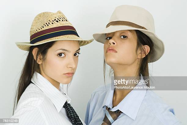Two young female friends wearing hats and ties, both looking at camera
