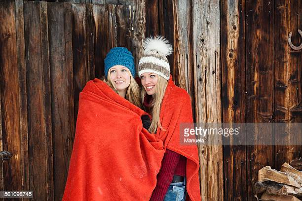 Two young female friends wrapped in red blanket outside wooden cabin