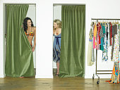 Two young female models in dressing rooms, smiling at one another