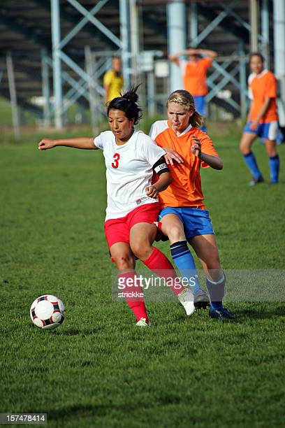 Two Young Female Soccer Players Battle Anticipate Ball