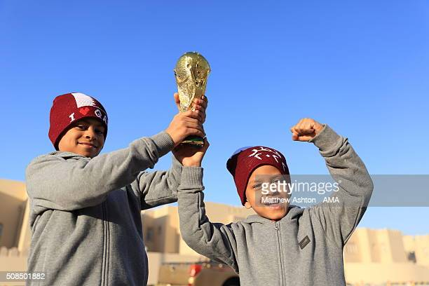 Two young football fans holding a replica of the FIFA World Cup Trophy in Doha Qatar the host venue for the FIFA World Cup Final 2022 whilst wearing...