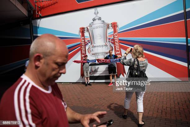 Two young football fans pose for a picture as people make their way to Wembley Stadium ahead of the FA Cup final on May 27 2017 in London England...