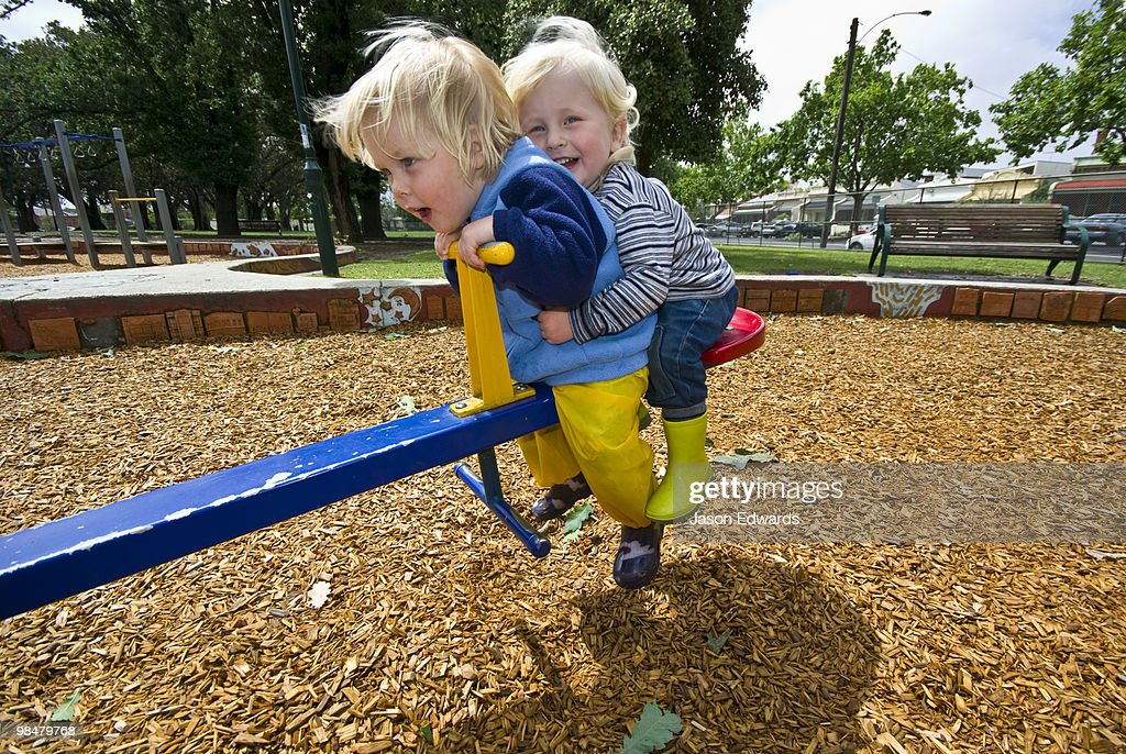 Two young friends enjoy a ride on a seesaw in a community playground. : Stock Photo
