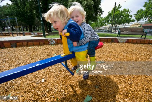 Two young friends enjoy a ride on a seesaw in a community playground. : ストックフォト