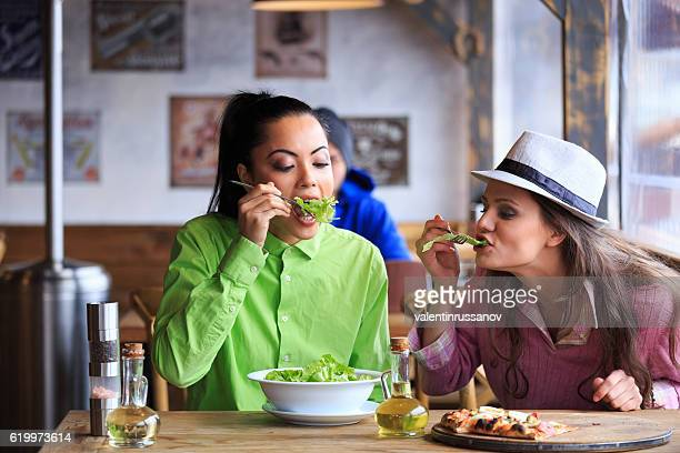 Two young friends having lunch in restaurant together
