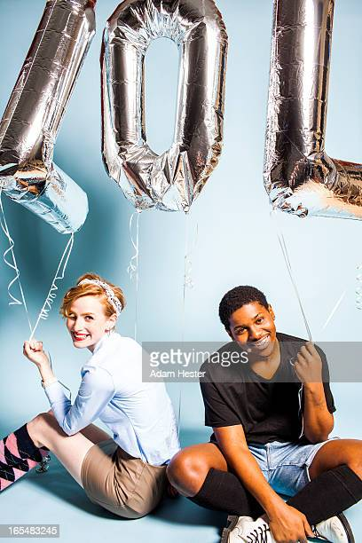 Two young friends holding letter balloons inside.