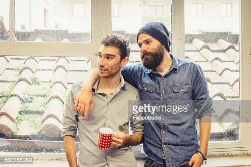 zwei junge freunde in der n he der fenster stock foto. Black Bedroom Furniture Sets. Home Design Ideas