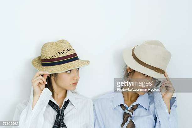 Two young friends pulling hats down over their faces, one looking at camera, portrait