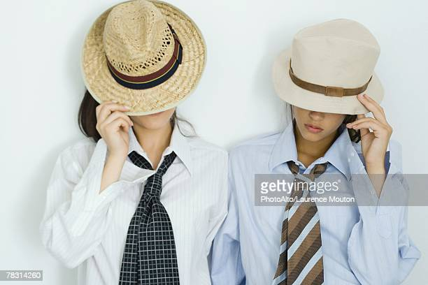 Two young friends pulling hats down over their faces, portrait