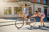 Two young friends relaxing on a hot summer day with one young woman riding a bicycle towing her friend on a skateboard down an urban street