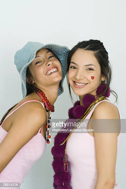 Two young friends smiling at camera together, portrait