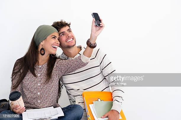 Two young friends taking photos of themselves against white background