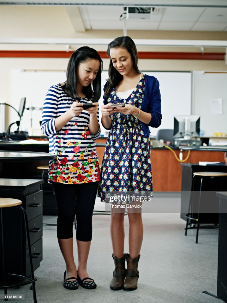 Two young friends using smart phones in classroom : Stock Photo