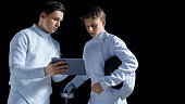 Two Young Fully Equipped Fencers Use Tablet Computer To Learn More About Strategy, Attack and Defense in Fencing. Shot Isolated on Black Background.